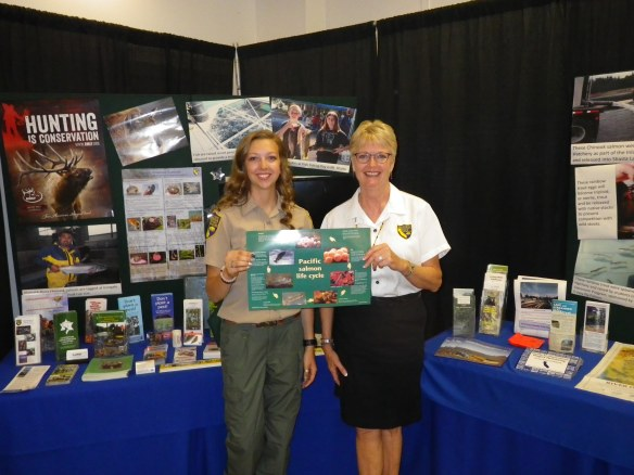 Fisheries Scientific Aid Torry Zimmerman and Outreach Coordinator Eda Eggeman put the finishing touches on the Shasta District Fair booth.  Outreach Team member Samantha Reece was also a key booth installer.